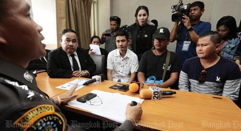 Miesten asianajaja (vas.) sekä osa uhreista rikosilmoitusta jättämässä Bangkokin poliisille.